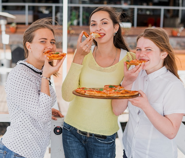 Amigos de tiro médio comendo pizza