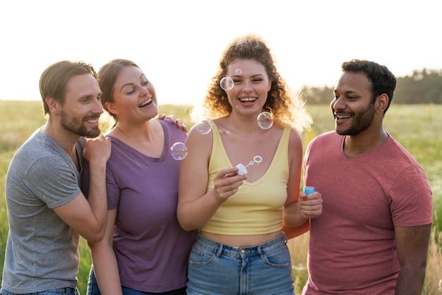 Amigos de tiro médio fazendo bolhas de sabão