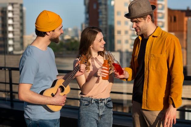 Amigos de tiro médio festejando com guitarra