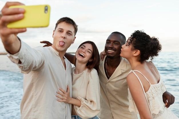 Amigos de tiro médio tirando selfie à beira-mar