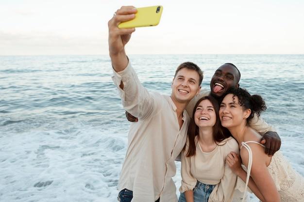 Amigos de tiro médio tirando selfie do lado de fora