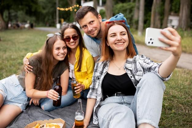Amigos de tiro médio tirando selfie na natureza