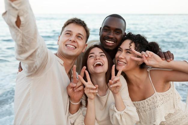 Amigos de tiro médio tirando selfie na praia