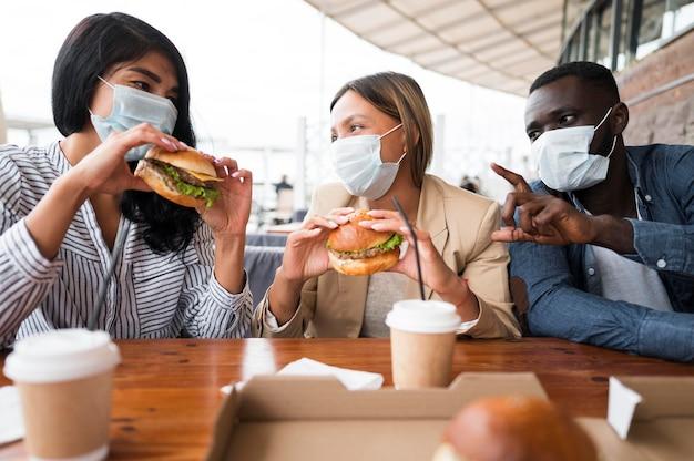 Amigos de tiro médio usando máscaras na mesa