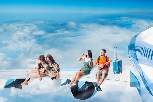 Amigos de turistas voam de férias e sentado na asa do avião de passageiros a jato. voo de dia.