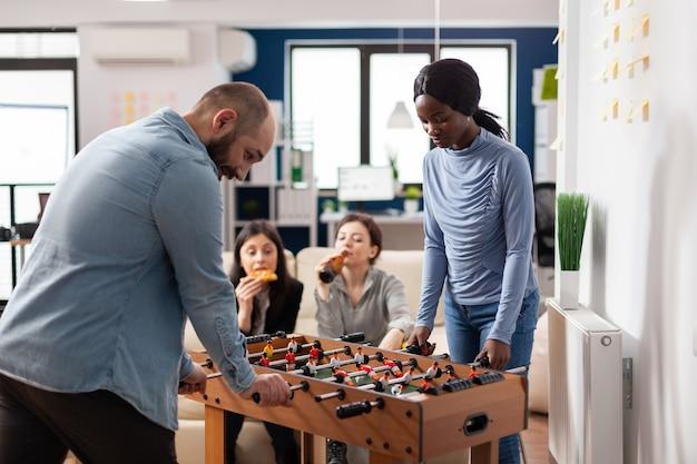 Amigos de várias etnias desfrutam de um jogo de pebolim depois do trabalho