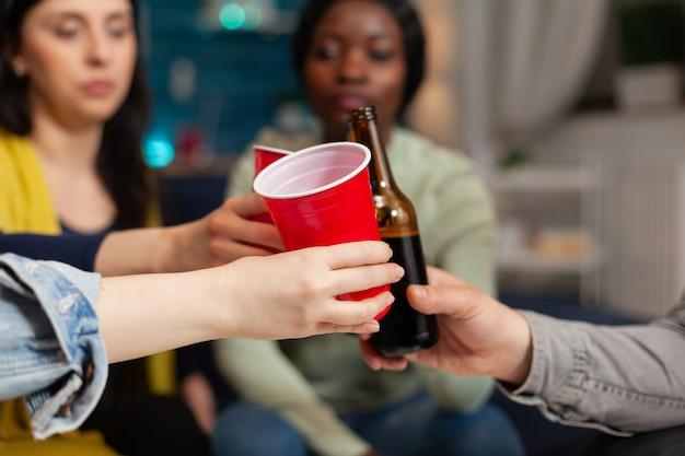 Amigos de várias etnias sentados no sofá conversando com copos de cerveja tilintantes. grupo de pessoas multirraciais, passando algum tempo juntos sentados no sofá à noite na sala de estar.