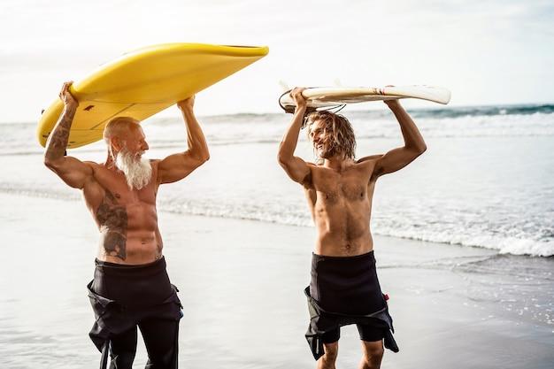 Amigos de várias gerações indo surfar em uma praia tropical - pessoas da família se divertindo fazendo esportes radicais - idoso alegre e conceito de estilo de vida saudável - foco principal no rosto do idoso