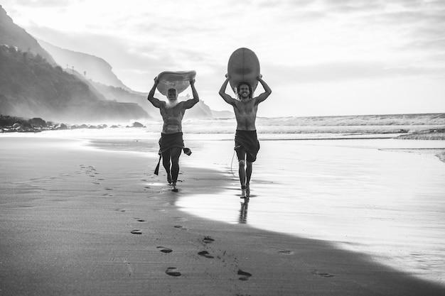 Amigos de várias gerações indo surfar na praia tropical - pessoas em família se divertindo praticando esportes radicais - foco principal no rosto jovem - edição em preto e branco