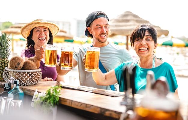 Amigos de várias idades brindando cerveja em chiringuito bar da praia