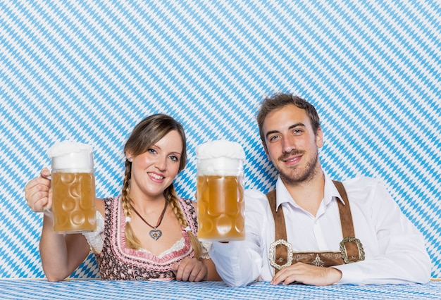 Amigos de vista frontal segurando canecas de cerveja