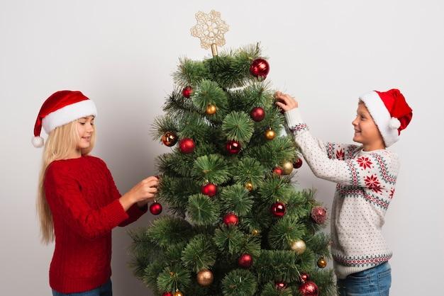 Amigos decorando a árvore de natal plano médio