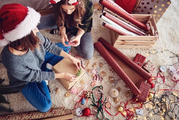 Amigos decorando um presente de natal
