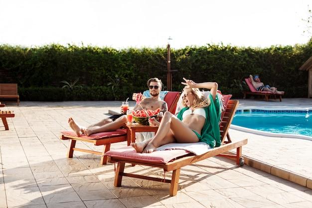Amigos, deitado nas espreguiçadeiras perto da piscina, fazendo selfie, sorrindo