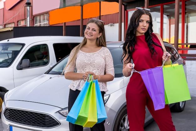 Amigos depois de fazer compras com sacolas coloridas perto do carro