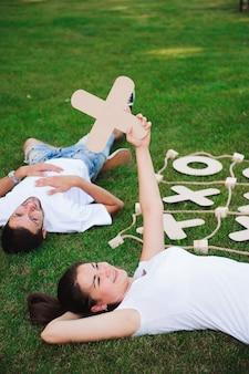 Amigos descansam e jogam jogo da velha na grama verde.