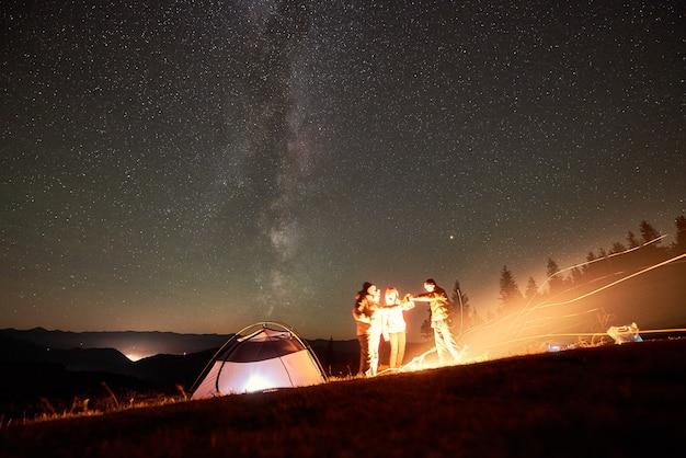 Amigos descansando ao lado do acampamento, fogueira sob o céu estrelado à noite