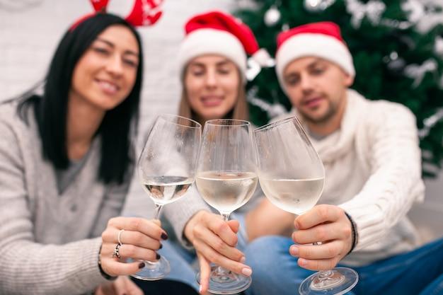Amigos desfocados bebem vinho perto da árvore de natal
