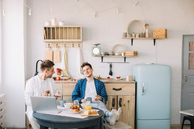 Amigos, desfrutando, café manhã, sentando, frente, tabela, em, cozinha