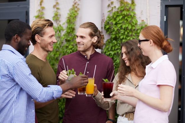 Amigos, desfrutando de bebidas na festa ao ar livre