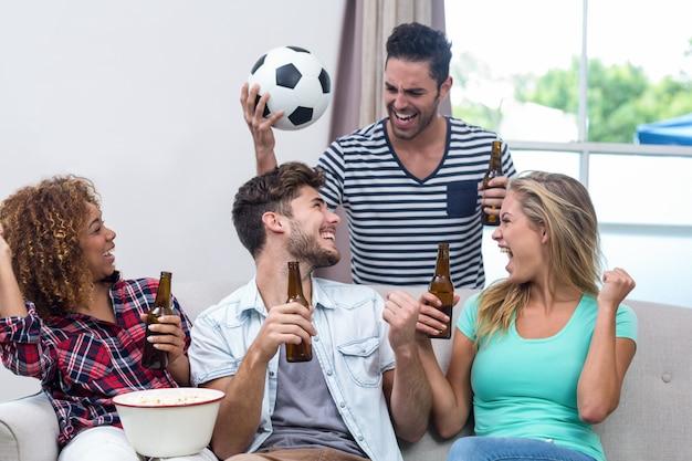Amigos, desfrutando de cerveja enquanto assistia jogo de futebol