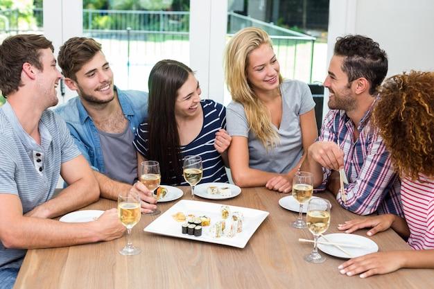Amigos desfrutando enquanto come sushi e vinho