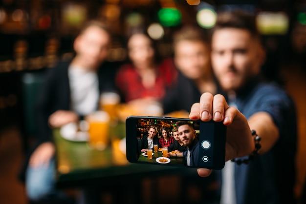 Amigos divertidos fazem selfie no telefone em um bar esportivo
