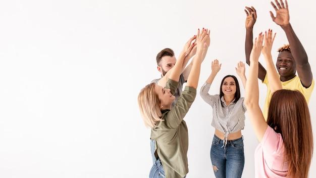 Amigos do espaço para cópia, juntamente com as mãos levantadas