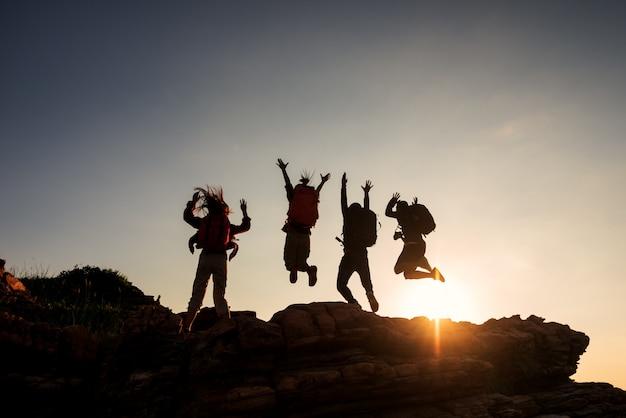 Amigos do grupo de escalada pulando na montanha superior e incrível céu pôr do sol.