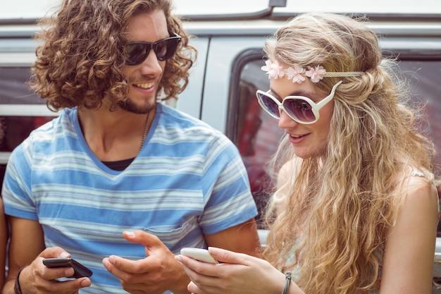 Amigos do hipster usando seus telefones