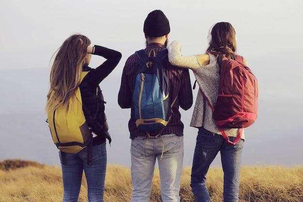 Amigos do homem com duas garotas fofas muito sensuais ou mulheres em pé com mochilas coloridas no topo da montanha