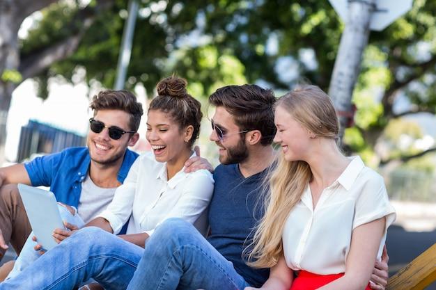 Amigos do quadril olhando para tablet e sentado na calçada