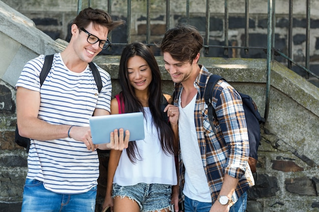 Amigos do quadril olhando para tablet na rua