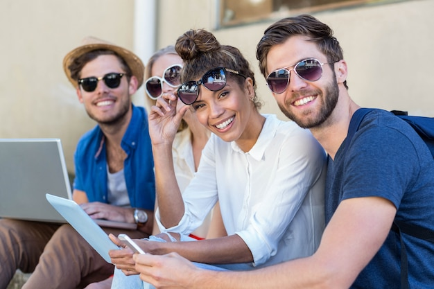 Amigos do quadril sentado na calçada e usando o laptop, tablet e smartphone