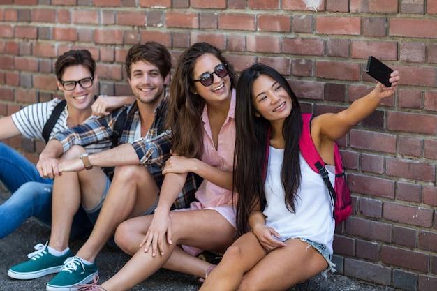Amigos do quadril sentado no chão e tendo selfie contra a parede de tijolos