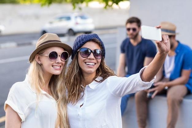 Amigos do quadril tomando selfies nas ruas