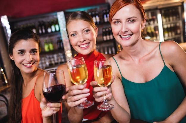 Amigos do sexo feminino a desfrutar de vinho em boate