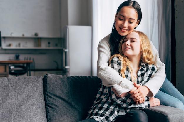 Amigos do sexo feminino abraçando ternamente em casa
