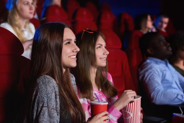 Amigos do sexo feminino alegres novos atrativos que apreciam assistindo a um filme no conceito das emoções da positividade da felicidade do entretenimento da recreação do cinema junto.