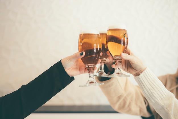 Amigos do sexo feminino bebendo cerveja e tilintar de copos no bar