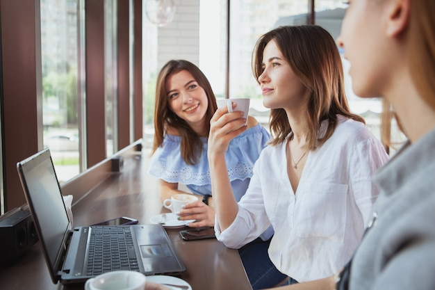 Amigos do sexo feminino bonitas desfrutando de café da manhã no café juntos