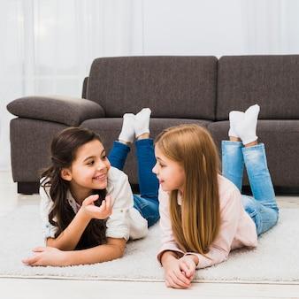 Amigos do sexo feminino bonitos deitado no tapete falando um com o outro