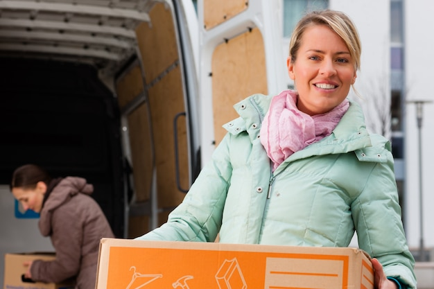 Amigos do sexo feminino carregando um caminhão em movimento