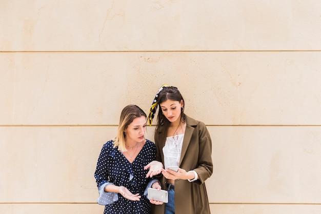 Amigos do sexo feminino chateados em frente a parede olhando para celular