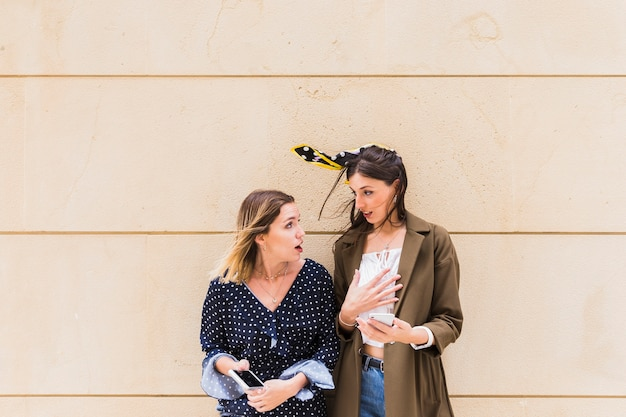 Amigos do sexo feminino chocados segurando o celular em frente a parede
