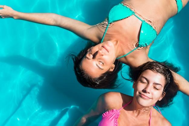 Amigos do sexo feminino com os olhos fechados na piscina