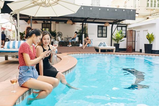 Amigos do sexo feminino com smartphone sentado na piscina