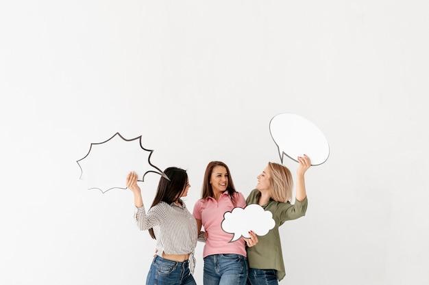 Amigos do sexo feminino cópia-espaço segurando bolha de bate-papo