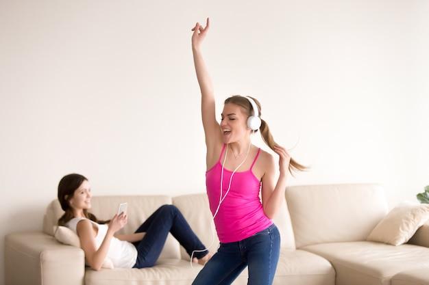 Amigos do sexo feminino entretém com gadgets digitais