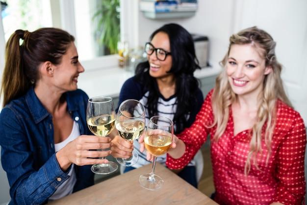 Amigos do sexo feminino felizes brindando um copo de vinho na mesa